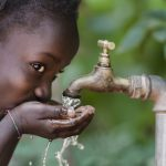 African Child Drinking Fresh Water From Tap